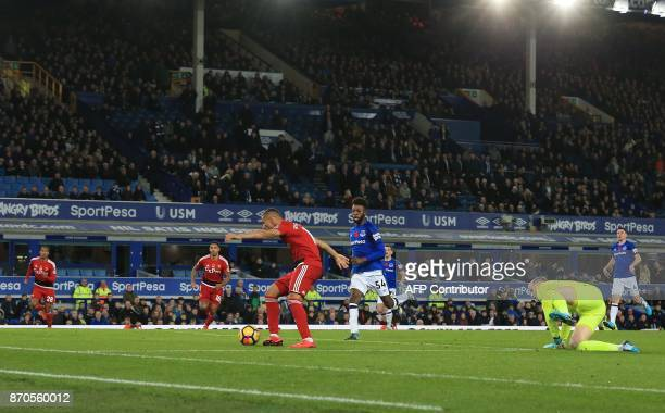 Watford's Brazilian striker Richarlison de Andrade beats Everton's English goalkeeper Jordan Pickford to score the opening goal during the English...