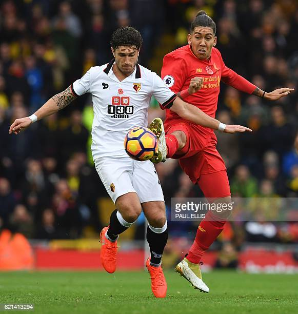 Watford's Dutch defender Daryl Janmaat vies with Liverpool's Brazilian midfielder Roberto Firmino during the English Premier League football match...