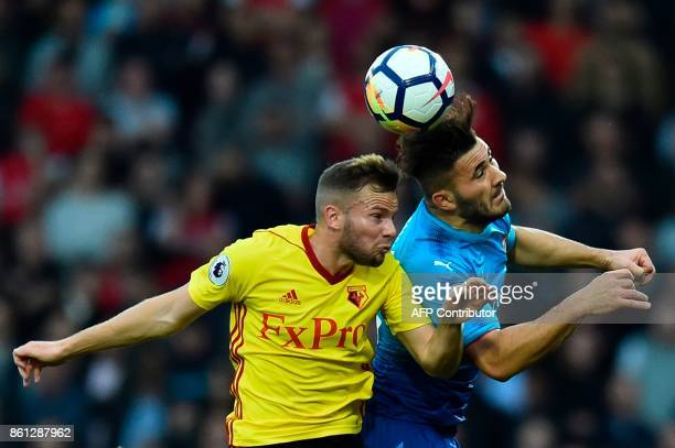 Watford's English mifielder Tom Cleverley goes up for a header with Arsenal's Germanborn Bosnian defender Sead Kolasinac during the English Premier...