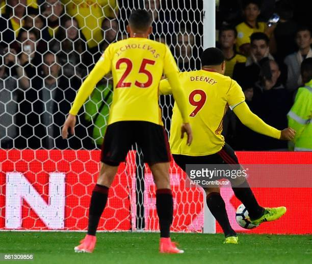 Watford's English striker Troy Deeney scores an equalising goal from the penalty spot for 11 during the English Premier League football match between...