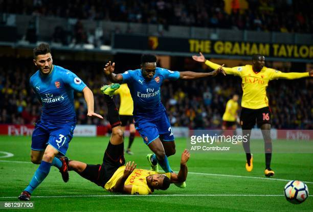 Watford's Englishborn Jamaican defender Adrian Mariappa goes down under a challenge from Arsenal's Germanborn Bosnian defender Sead Kolasinac and...