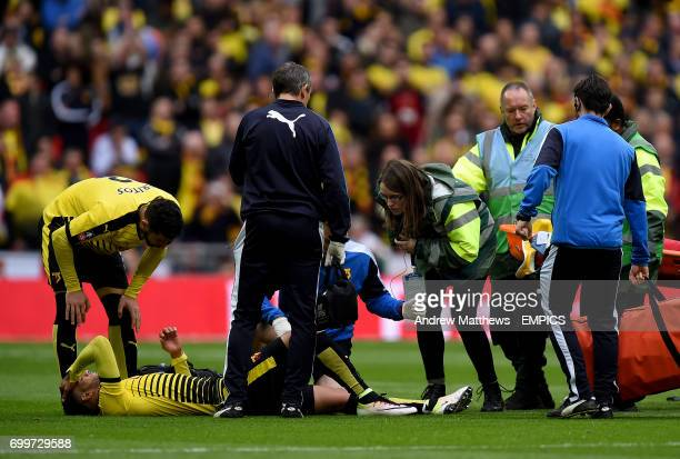 Watford's Etienne Capoue lies injured on the ground as medical staff treat him