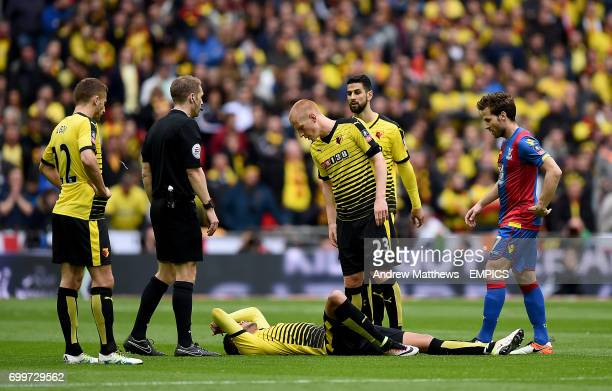 Watford's Etienne Capoue lies injured on the ground as teammate Watford's Ben Watson stands over him