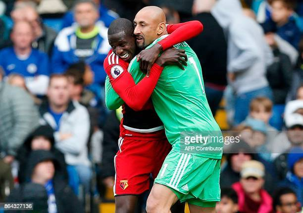 Watford's French midfielder Abdoulaye Doucoure celebrates scoring his team's first goal with Watford's Brazilian goalkeeper Heurelho Gomes during the...