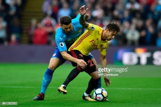 Watford's Spanish defender Kiko Femenia tangles with Arsenal's Germanborn Bosnian defender Sead Kolasinac during the English Premier League football...