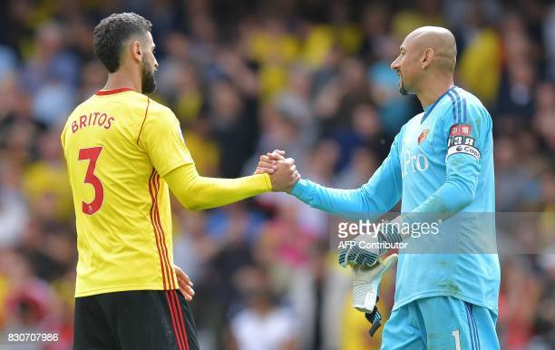 Watford's Uruguayan defender Miguel Britos shakes hands with Watford's Brazilian goalkeeper Heurelho Gomes following the English Premier League...