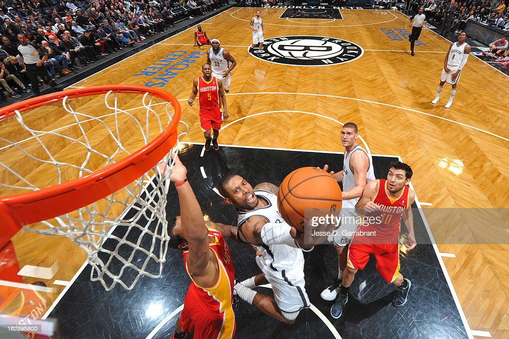 C.J. Watson #1 of the Brooklyn Nets goes to the basket against Greg Smith #4 and Carlos Delfino #10 of the Houston Rockets at the Barclays Center on February 22, 2013 in Brooklyn, New York.