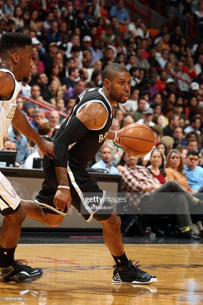 C.J. Watson #1 of the Brooklyn Nets handles the ball against Norris Cole #30 of the Miami Heat on December 1, 2012 at American Airlines Arena in Miami, Florida.