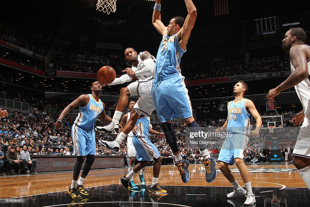 C.J. Watson #1 of the Brooklyn Nets passes in mid-air against the Denver Nuggets at the Barclays Center on February 13, 2013 in the Brooklyn borough of New York City in New York City.