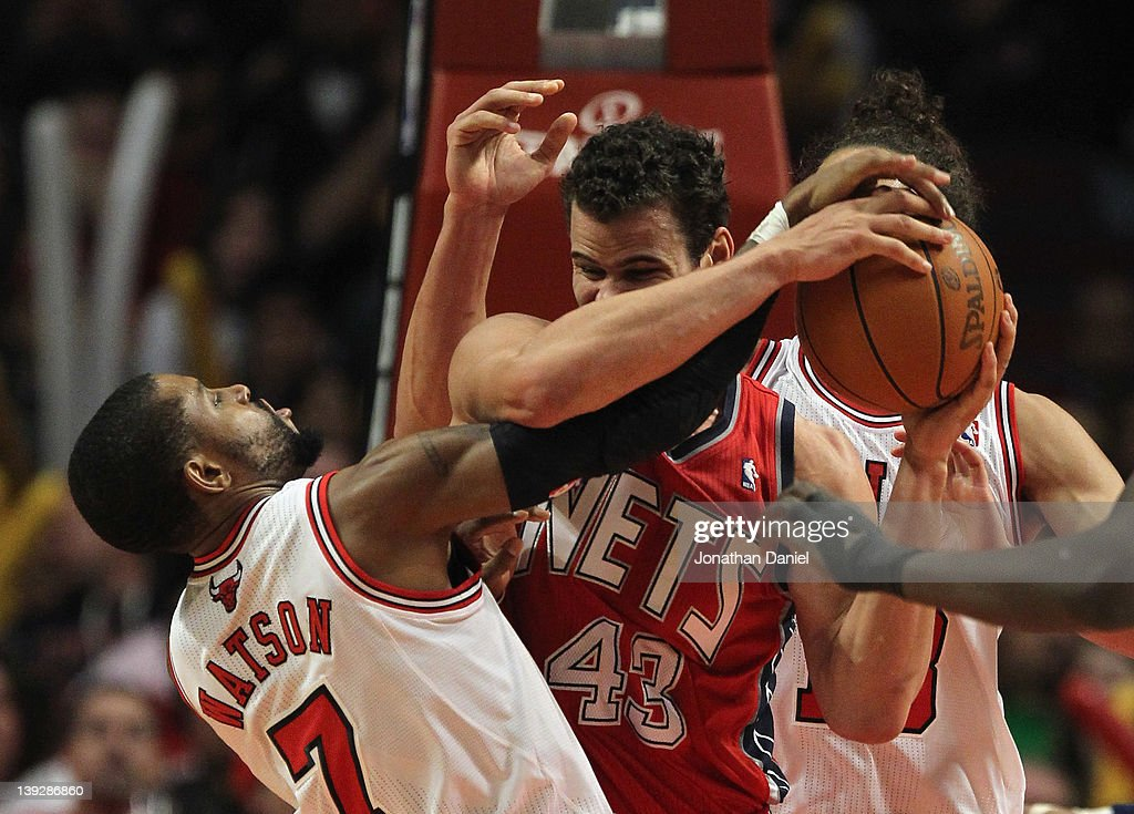 J Watson of the Chicago Bulls gets his hand on the ball as Kris Humphries of the New Jersey Nets grabs a rebound at the United Center on February 18...