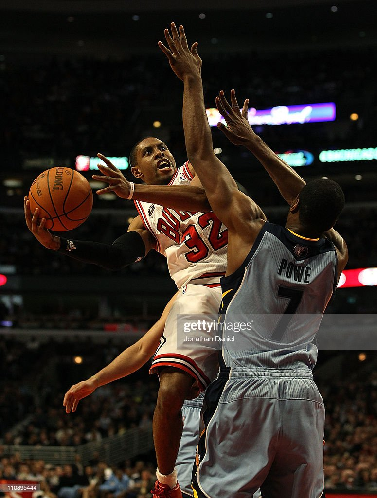 J Watson of the Chicago Bulls moves around Leon Powe of the Memphis Grizzlies to put up a shot at the United Center on March 25 2011 in Chicago...