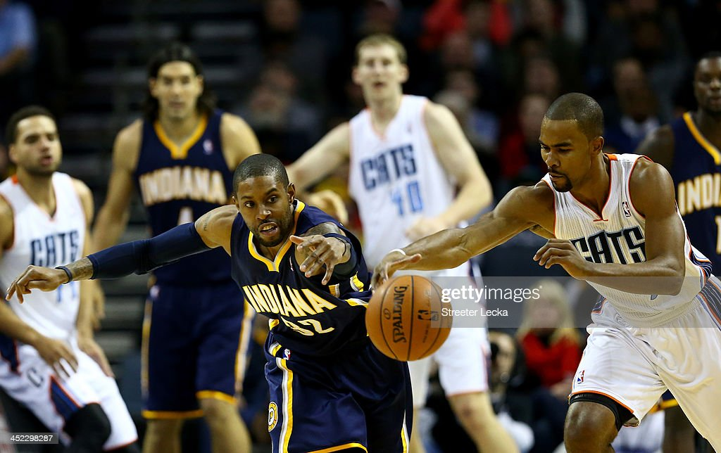 J Watson of the Indiana Pacers goes after a loose ball with Ramon Sessions of the Charlotte Bobcats during their game at Time Warner Cable Arena on...