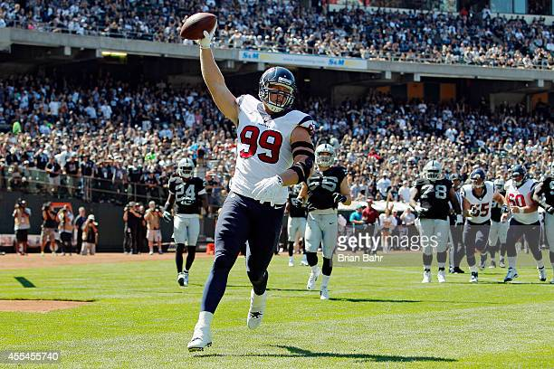 J Watt of the Houston Texans celebrates after scoring a touchdown against the Oakland Raiders in the first quarter on September 14 2014 at Oco...