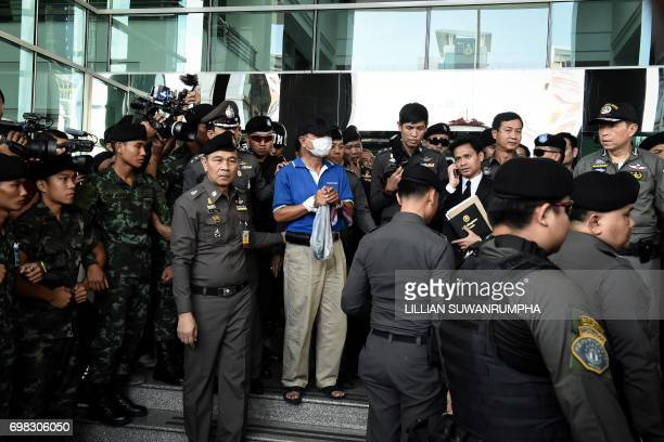 Wattana Phumret a suspect in the bombing of a military hospital on May 22 is escorted by Thai police during a crime reenactment at King Mongkut...