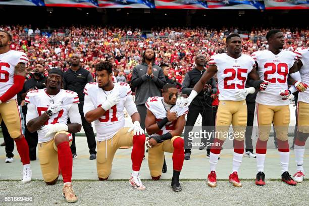 Waun Williams Arik Armstead and Eli Harold of the San Francisco 49ers kneel while holding their hands over their chest during the US national anthem...