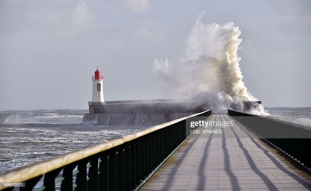 A wave breaks against a pier in front of a lighthouse in Les Sables-d'Olonne, western France, on February 9, 2016. High winds buffeted northwestern Europe on February 8, leaving one woman in France in a coma after she was hit by an advertising hoarding. Electricity was cut to 5,000 homes in northern France. / AFP / LOIC VENANCE