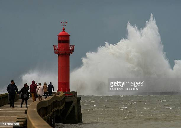 A wave breaks against a pier in front of a lighthouse in Wimereux on March 28 2016 Tens of thousands of homes were without power in northwestern...