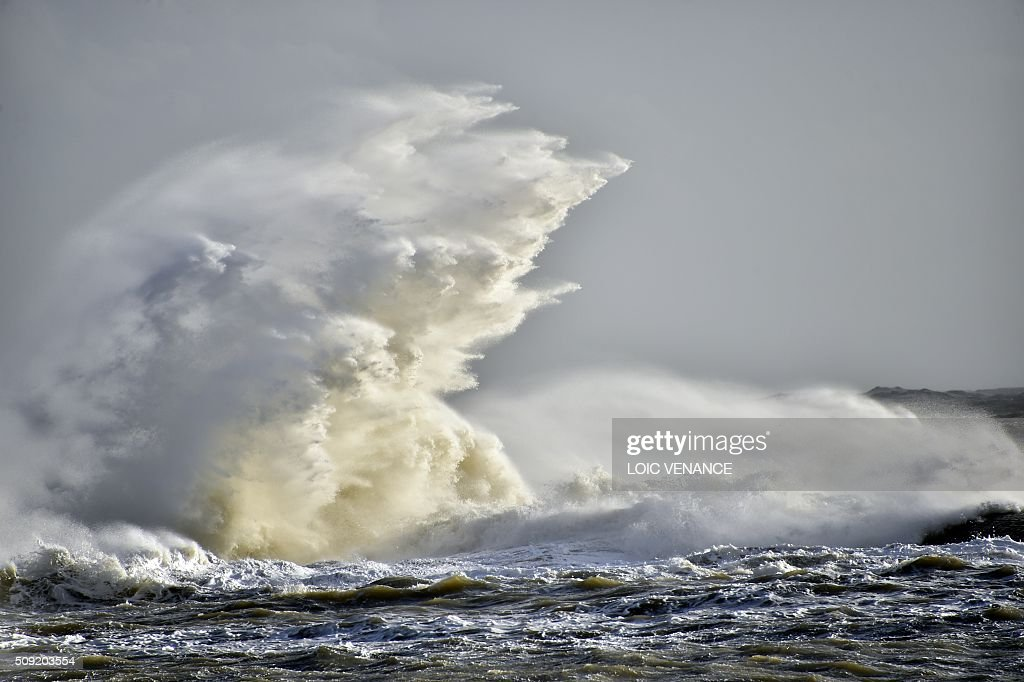 A wave breaks against a pier in Les Sables-d'Olonne, western France, on February 9, 2016. High winds buffeted northwestern Europe on February 8, leaving one woman in France in a coma after she was hit by an advertising hoarding. Electricity was cut to 5,000 homes in northern France. / AFP / LOIC VENANCE