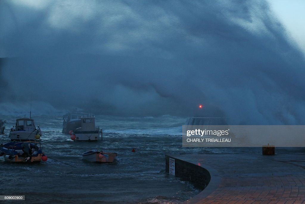 A wave breaks in the harbour in Auderville, northwestern France, on February 8, 2016, as strong winds hit the region. Winds of over 130 kh/h were recorded in the region where 16 departments have been placed under alert for wind and flooding waves. / AFP / CHARLY TRIBALLEAU