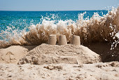 A Wave Crashes Over a Sandcastle