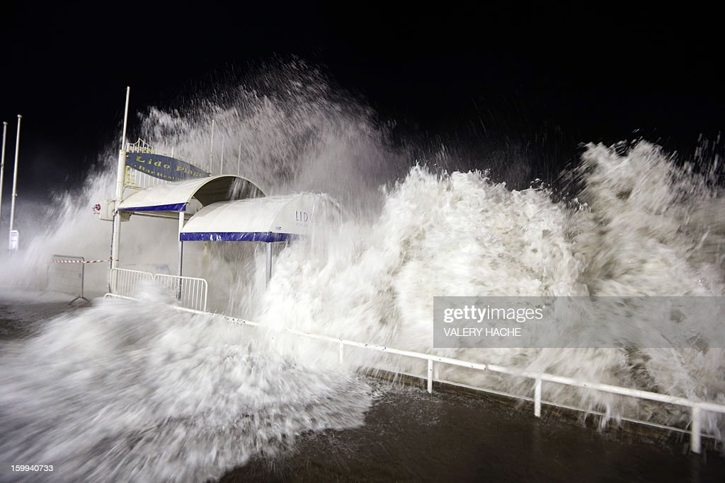 A wave crashes over the breakwater on the infamous Promenade des Anglais in Nice, southern France on January 23, 2013. France's meteorological bureau issued an alert mid-afternoon warning of high seas and winds. AFP PHOTO / VALERY HACHE