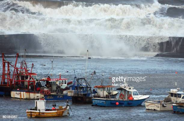 A wave crashes over the harbour wall at high tide on March 10 2008 in Lyme Regis United Kingdom Weather forecasters are saying parts of the UK are...