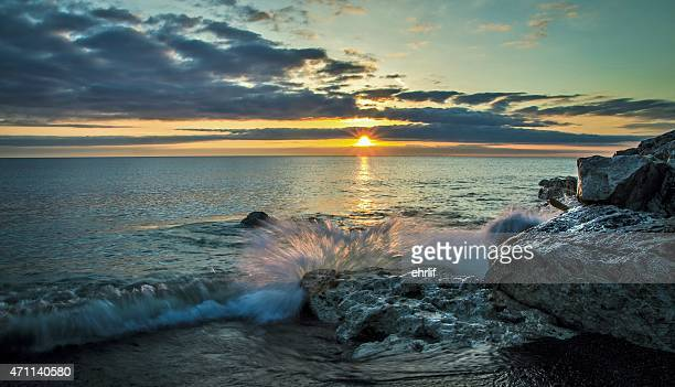 A single wave crashes over a rocky shore with a sunrise sky as a new day dawns. This is Tierney Park in Lexington, Michigan. Lexington is a quaint and popular resort town located on the shores of Lake Huron.