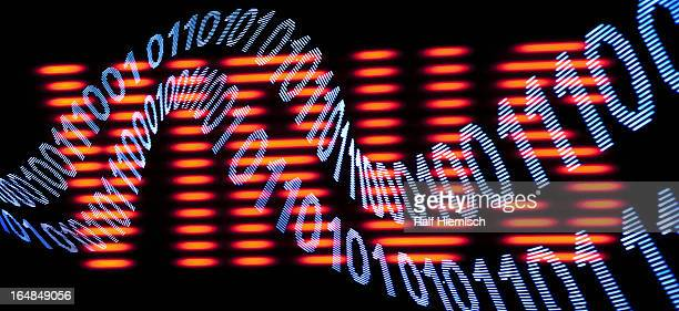 A wave pattern of binary code in front of a sign spelling VIRUS
