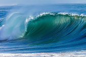 Ocean wave with colour curling crashing hollow wall of sea water onto shallow beach sandbanks