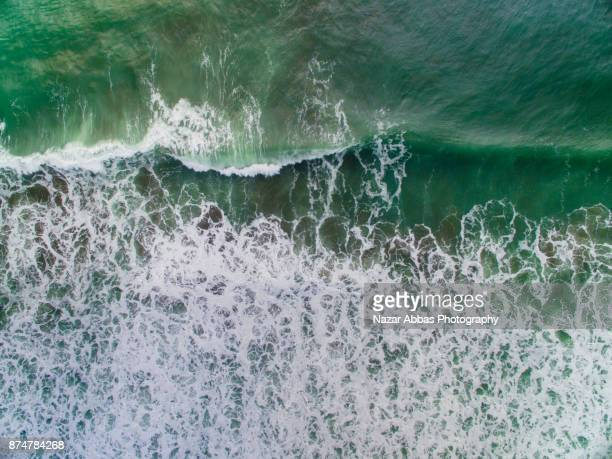 Wave splashing at sea with aerial view.