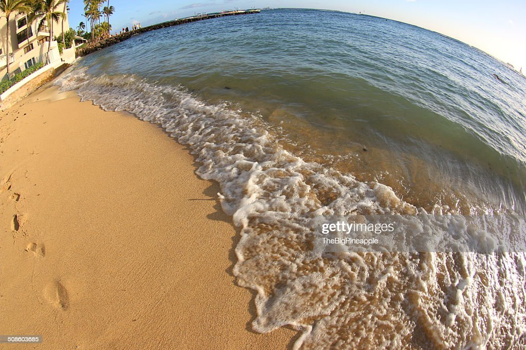 Wave washes up on sandy beach : Foto de stock
