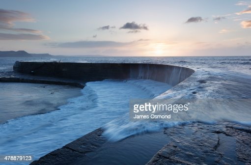 Wave washing over sea wall at sunrise