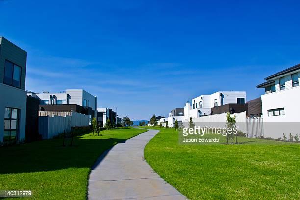 A pedestrian path through a linear park between new suburban homes.