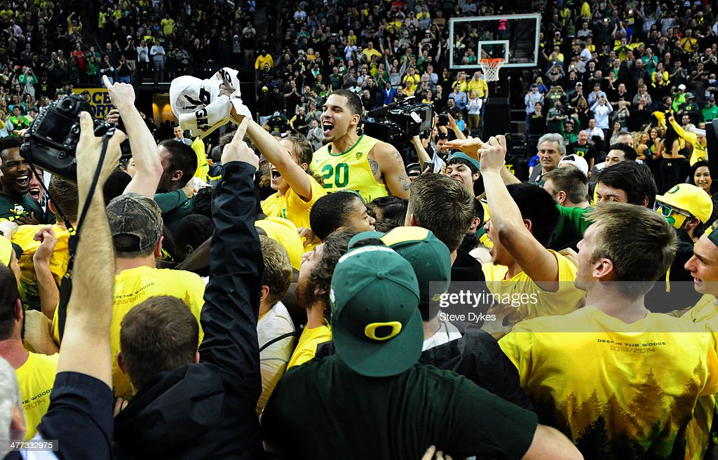 Waverly Austin #20 of the Oregon Ducks is lifted up in the air by Oregon fans who stormed the court after the game against the Arizona Wildcats at Matthew Knight Arena on March 8, 2014 in Eugene, Oregon. Oregon won the game 64-57.