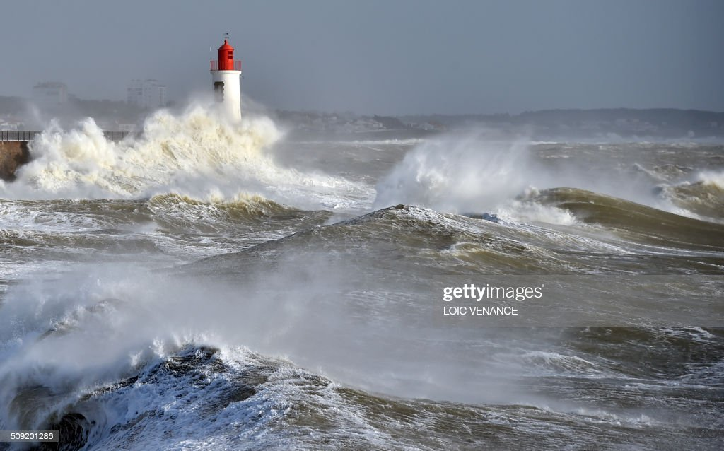 Waves break against a pier and a lighthouse in Les Sables-d'Olonne, western France, on February 9, 2016. High winds buffeted northwestern Europe on February 8, leaving one woman in France in a coma after she was hit by an advertising hoarding. Electricity was cut to 5,000 homes in northern France. / AFP / LOIC VENANCE