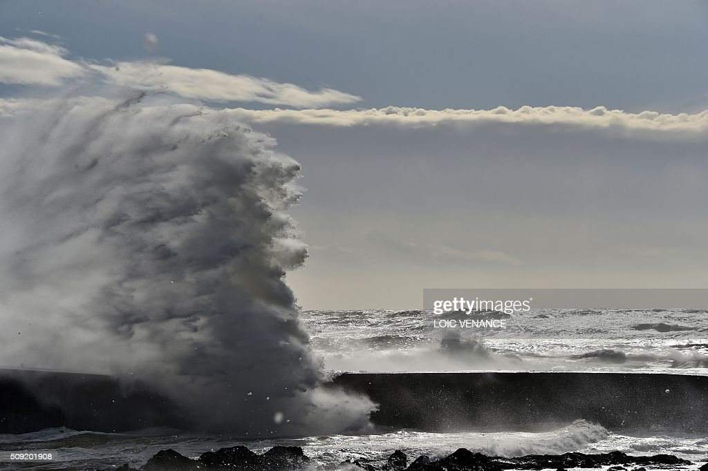 Waves break against a pier in Les Sables-d'Olonne, western France, on February 9, 2016. High winds buffeted northwestern Europe on February 8, leaving one woman in France in a coma after she was hit by an advertising hoarding. Electricity was cut to 5,000 homes in northern France. / AFP / LOIC VENANCE