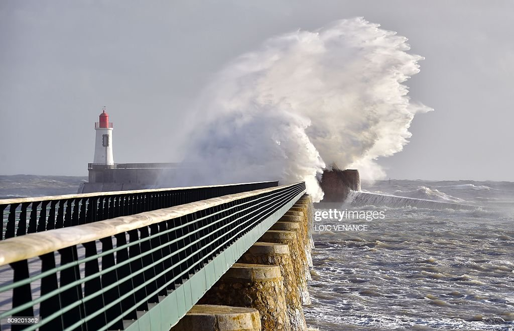 Waves break against a pier next to a lighthouse in Les Sables-d'Olonne, western France, on February 9, 2016. High winds buffeted northwestern Europe on February 8, leaving one woman in France in a coma after she was hit by an advertising hoarding. Electricity was cut to 5,000 homes in northern France. / AFP / LOIC VENANCE