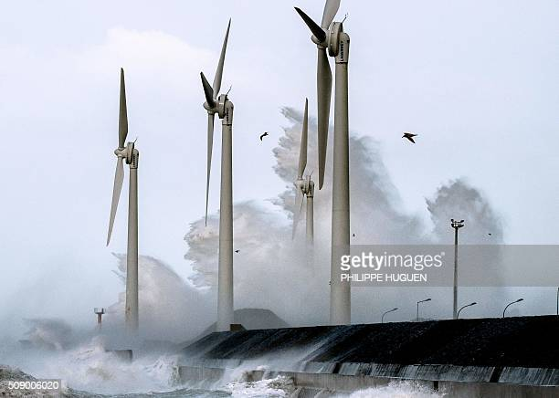 Waves break against the Boulognesurmer harbour pier where wind turbines stand on February 8 2016 Winds of over 130 kh/h were recorded in the country...