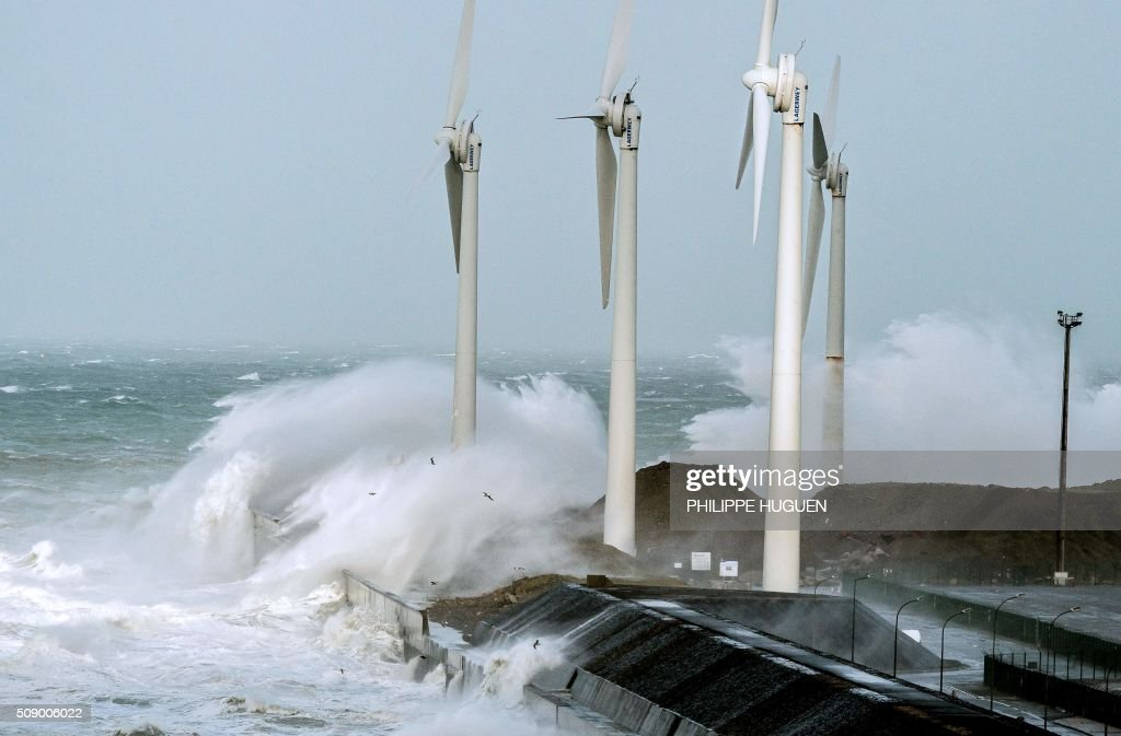 Waves break against the Boulogne-sur-mer harbour pier where wind turbines stand on February 8, 2016. Winds of over 130 kh/h were recorded in the country where 16 departments have been placed under alert for wind and flooding waves. / AFP / PHILIPPE HUGUEN