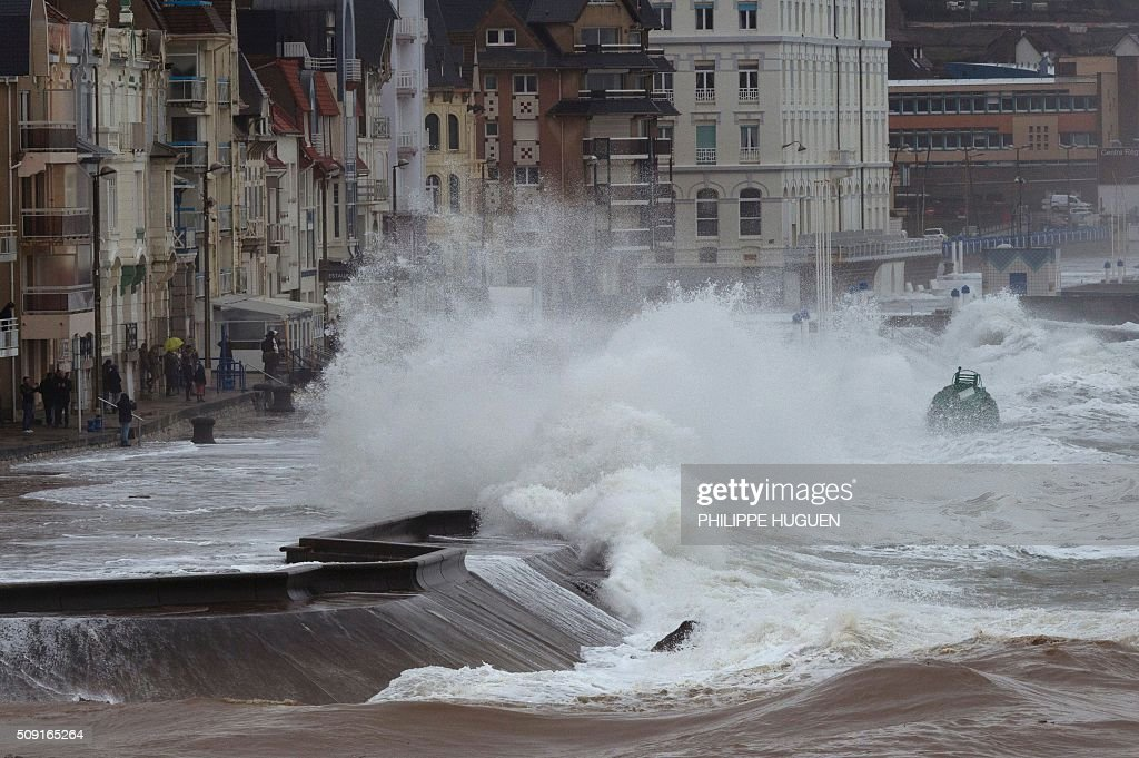 Waves break against the Wimereux breakwater, northern France, on February 9, 2016. High winds buffeted northwestern Europe on February 8, leaving one woman in France in a coma after she was hit by an advertising hoarding. Electricity was cut to 5,000 homes in northern France. / AFP / PHILIPPE HUGUEN