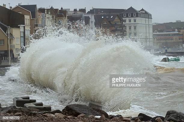 Waves break against the Wimereux breakwater northern France on February 9 2016 High winds buffeted northwestern Europe on February 8 leaving one...