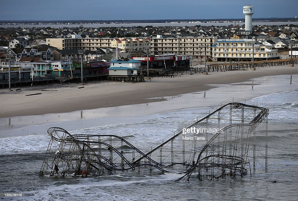 Waves break in front of a destroyed roller coaster wrecked by Superstorm Sandy on October 31, 2012 in Seaside Heights, New Jersey. At least 50 people were reportedly killed in the U.S. by Sandy with New Jersey suffering massive damage and power outages.