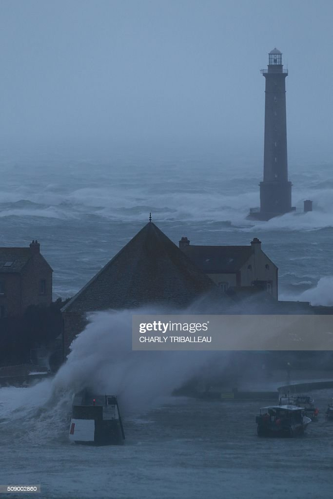 Waves break near the lighthouse in the harbour in Auderville, northwestern France, on February 8, 2016, as strong winds hit the region. Winds of over 130 kh/h were recorded in the region where 16 departments have been placed under alert for wind and flooding waves. / AFP / CHARLY TRIBALLEAU