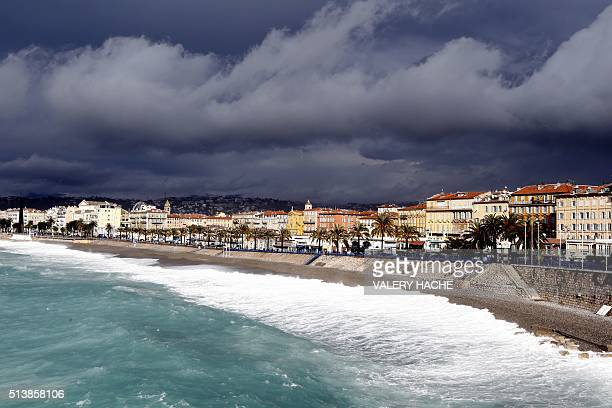 Waves break on the beach below the 'Promenade des Anglais' as clouds gather above the French Riviera city of Nice on March 5 2016 / AFP / VALERY HACHE