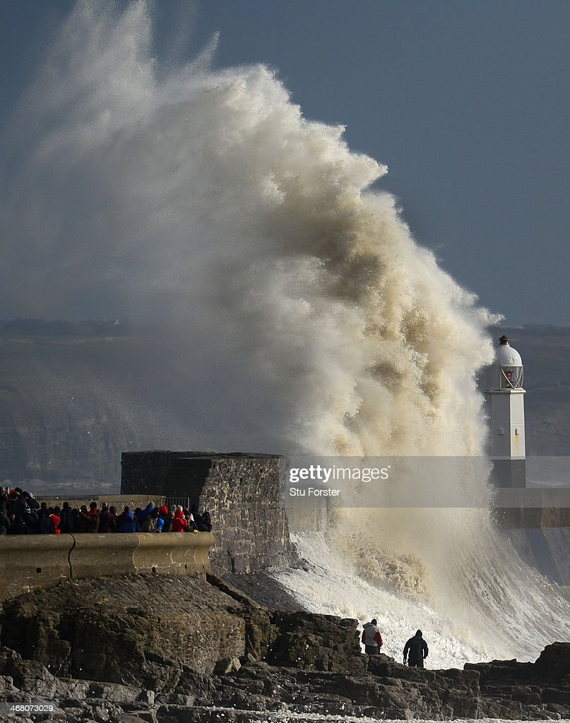 Waves break over the harbour wall during high tide as people watch on February 9 2014 in Porthcawl United Kingdom