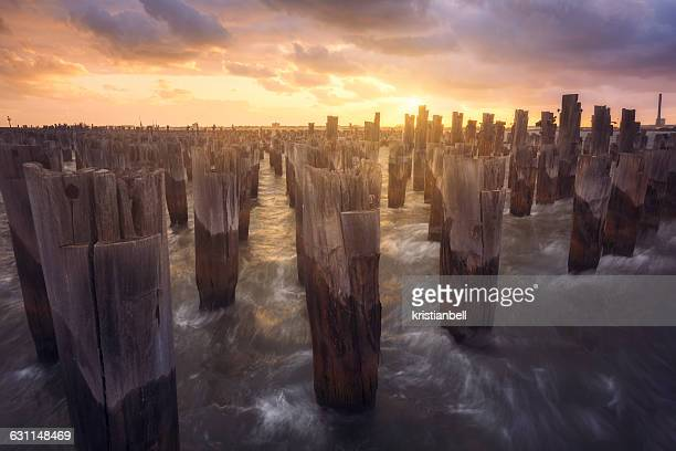 Waves breaking against wooden pier pilings, Melbourne, Victoria, Australia