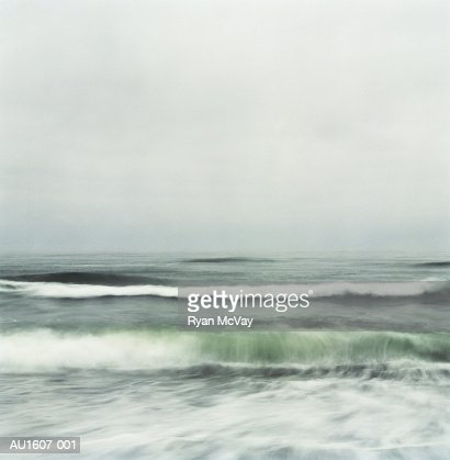 Waves breaking on beach, dusk (blurred motion) : Stock Photo