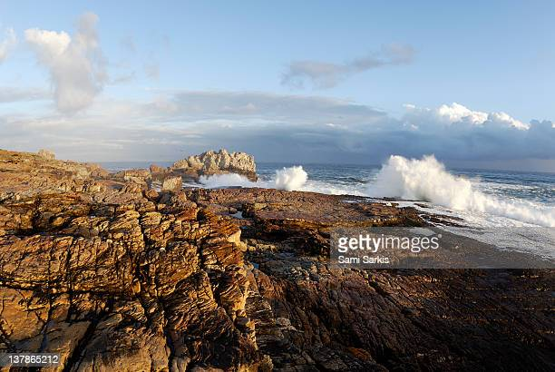 Waves breaking on rocky shore at sunset