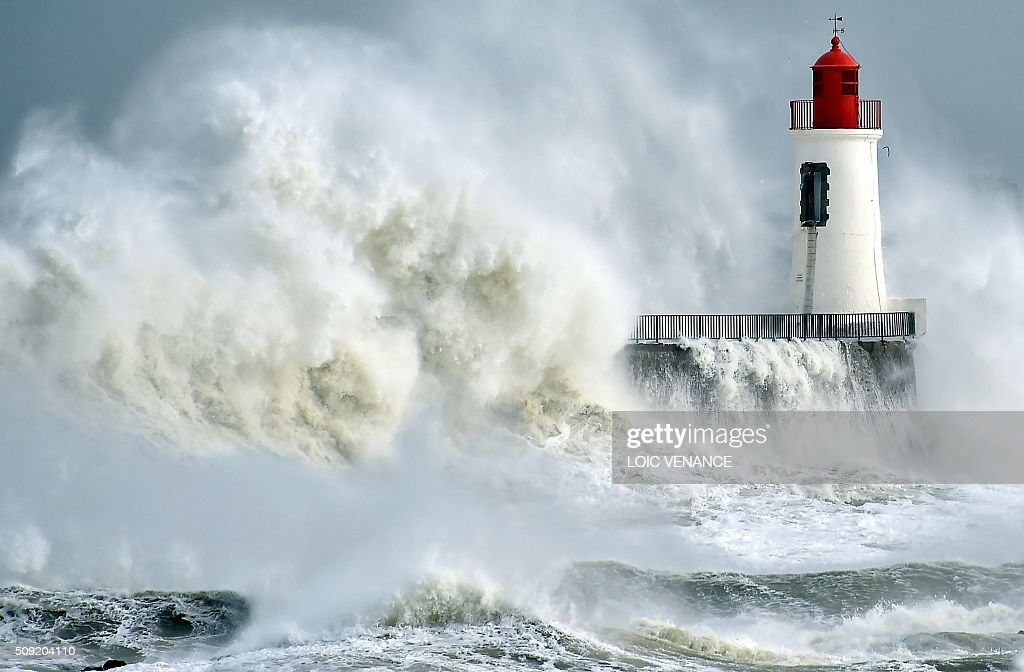 A waves breaks against a pier and a lighthouse in Les Sables-d'Olonne, western France, on February 9, 2016. High winds buffeted northwestern Europe on February 8, leaving one woman in France in a coma after she was hit by an advertising hoarding. Electricity was cut to 5,000 homes in northern France. / AFP / LOIC VENANCE
