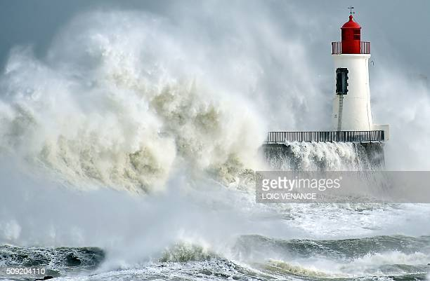 TOPSHOT A waves breaks against a pier and a lighthouse in Les Sablesd'Olonne western France on February 9 2016 High winds buffeted northwestern...